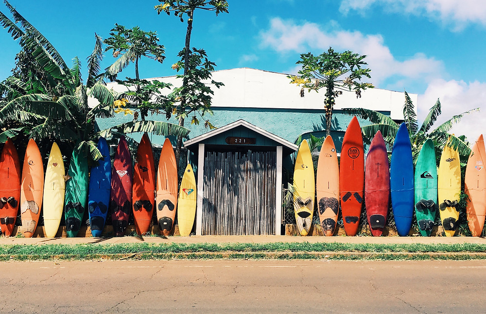 Surfboards lined up in front of a beach house