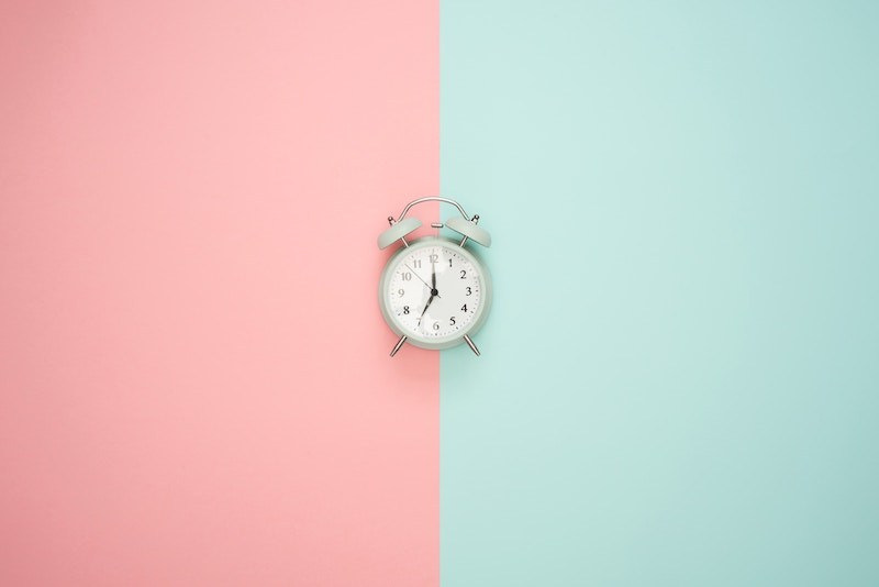 Old fashioned clock on a pink and blue surface