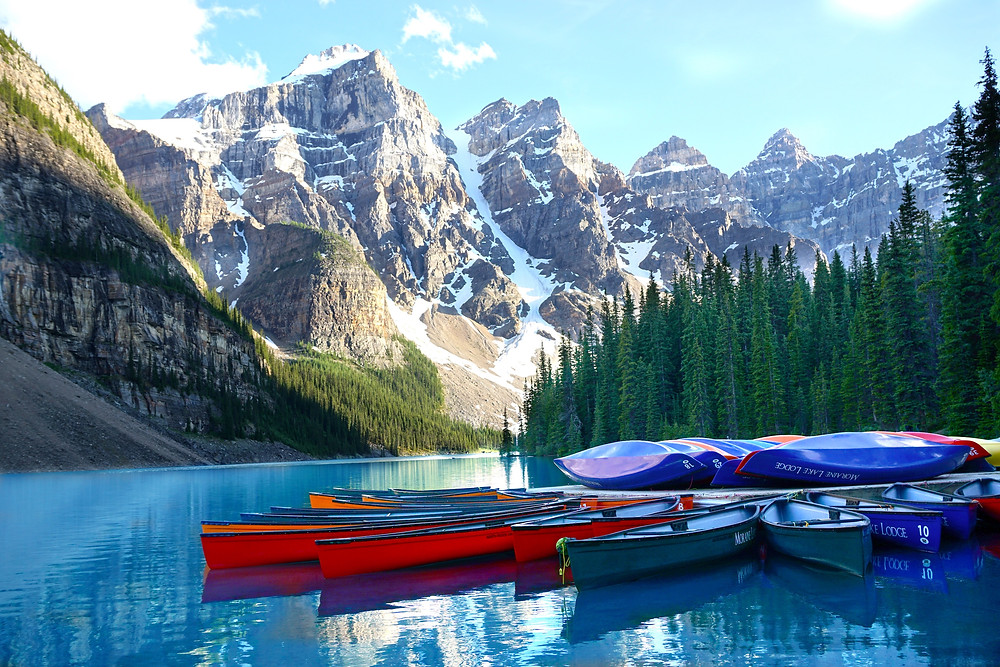 Canoes floating in the pristine surface of Lake Moraine in Banff, in addition to colorful kayaks stacked on the dock.