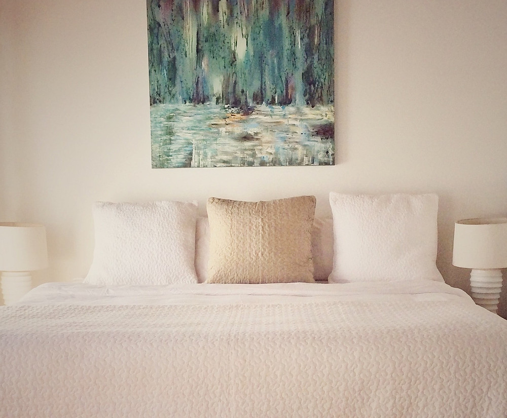 Photo of a bed with a teal, abstract painting above it in The Beach House B&B in Roatan's West End.