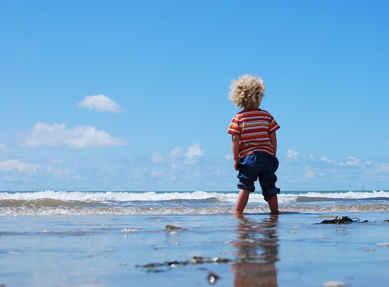 Child with blonde curly hair, a red striped shirt and jeans rolled up standing at the edge of the ocean under a blue sky