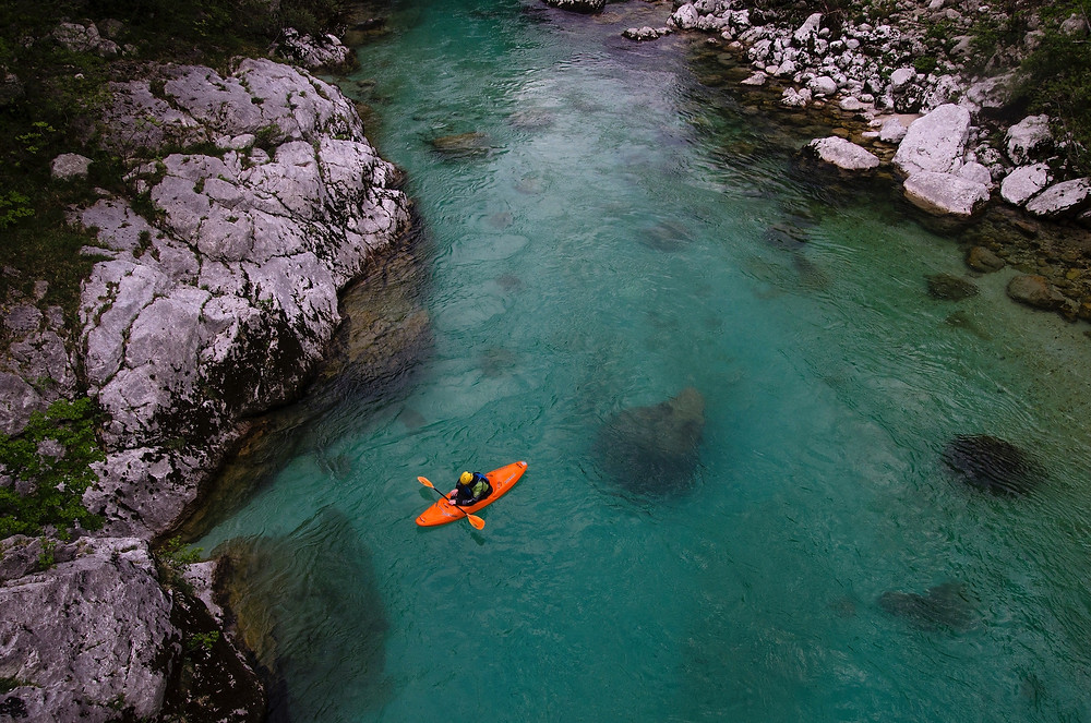 Person in an orange kayak in a blue river during an adventure vacation