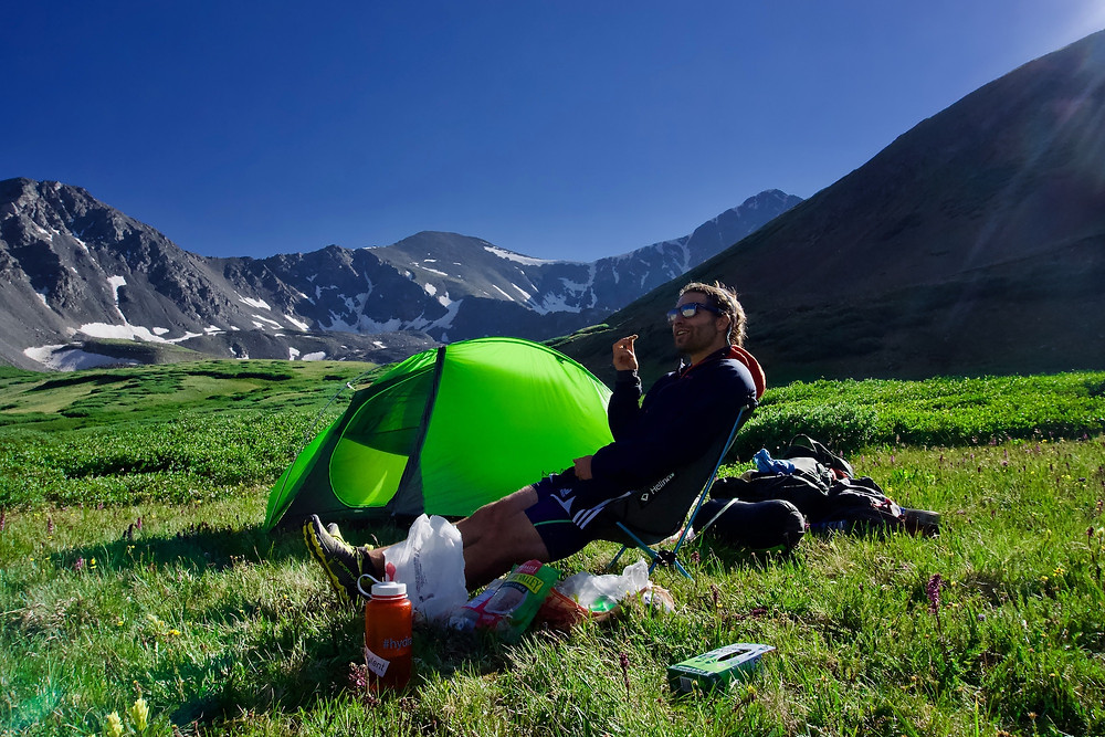 Man sitting in a camping chair in front of a green tent in a lush, grassy valley surrounded by mountains.