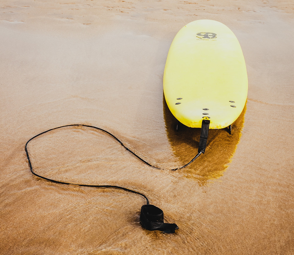 Yellow surfboard and leash on wet sand at beach
