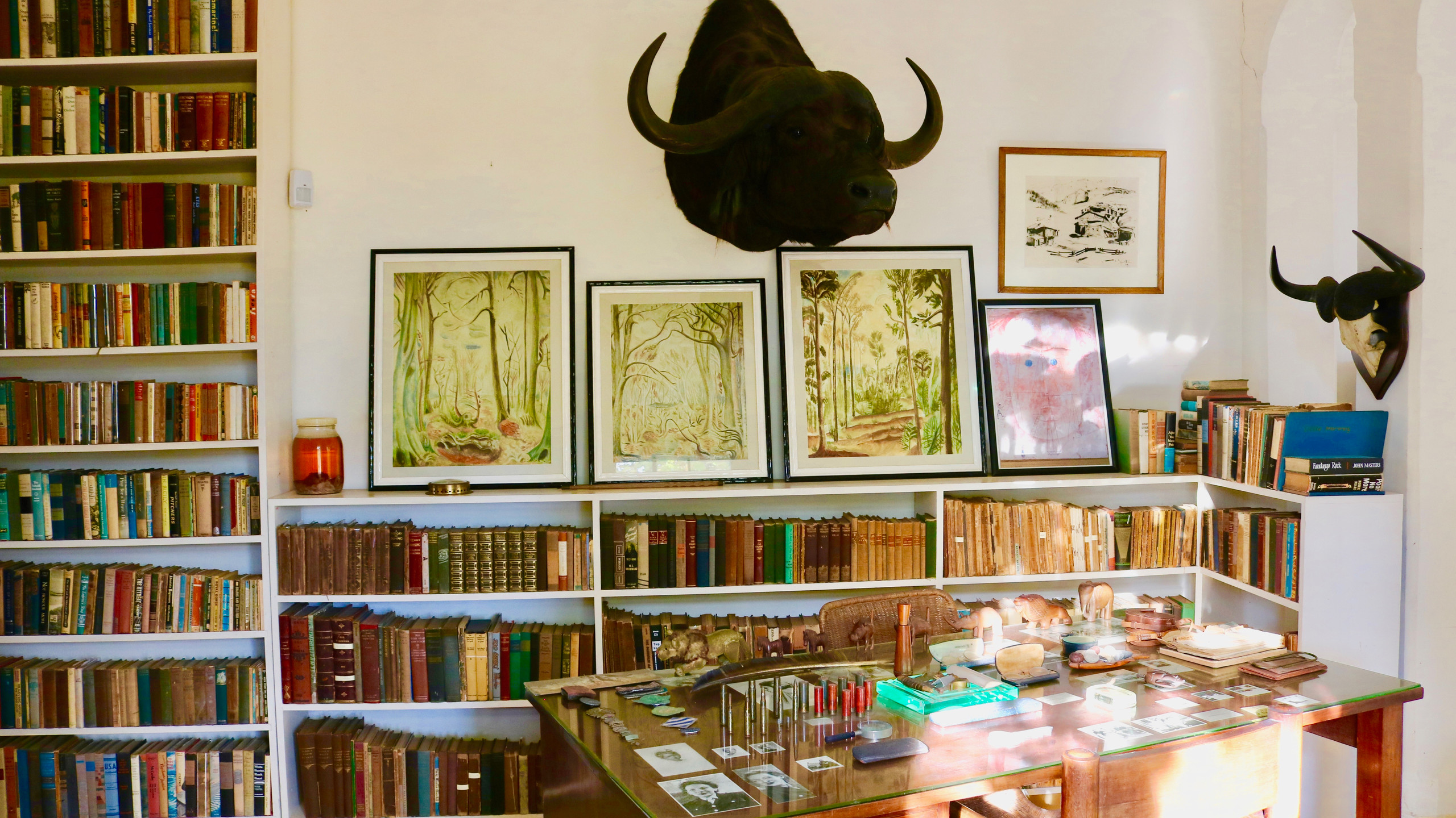 Desk in Ernest Hemingway's Finca Vigia home surrounded by colorful books.