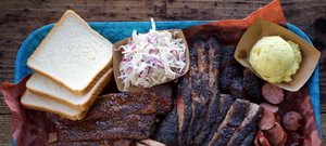 Plate of brisket, ribs, coleslaw, potato salad, and white bread at Franklin Barbeque.