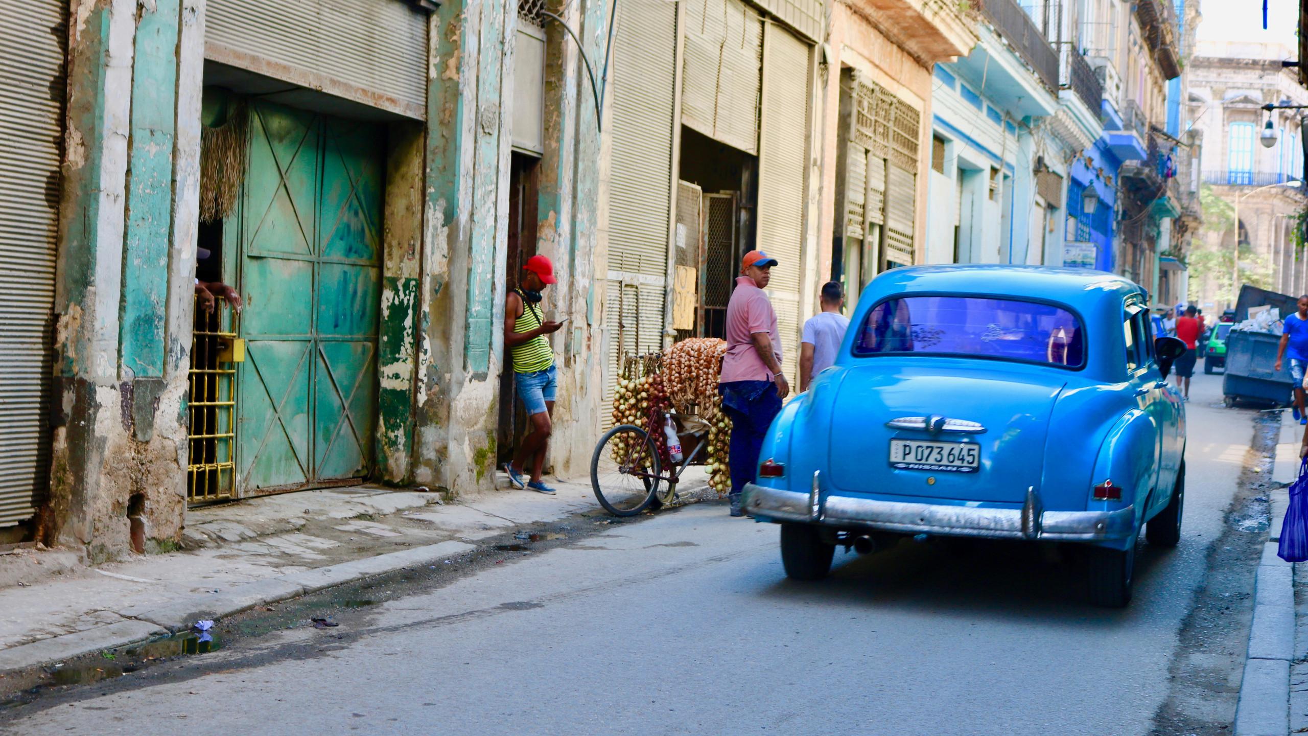 1950s blue car on a narrow street in Old Havana.