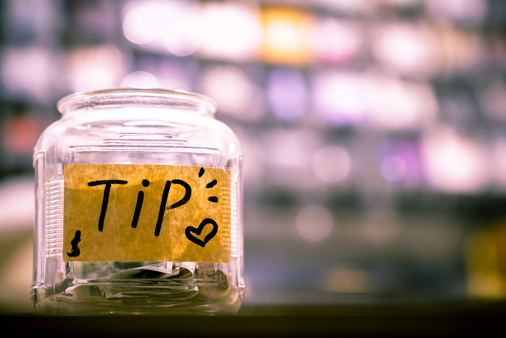 A tip jar with money inside it, representing the automatic tips cruise ships charge