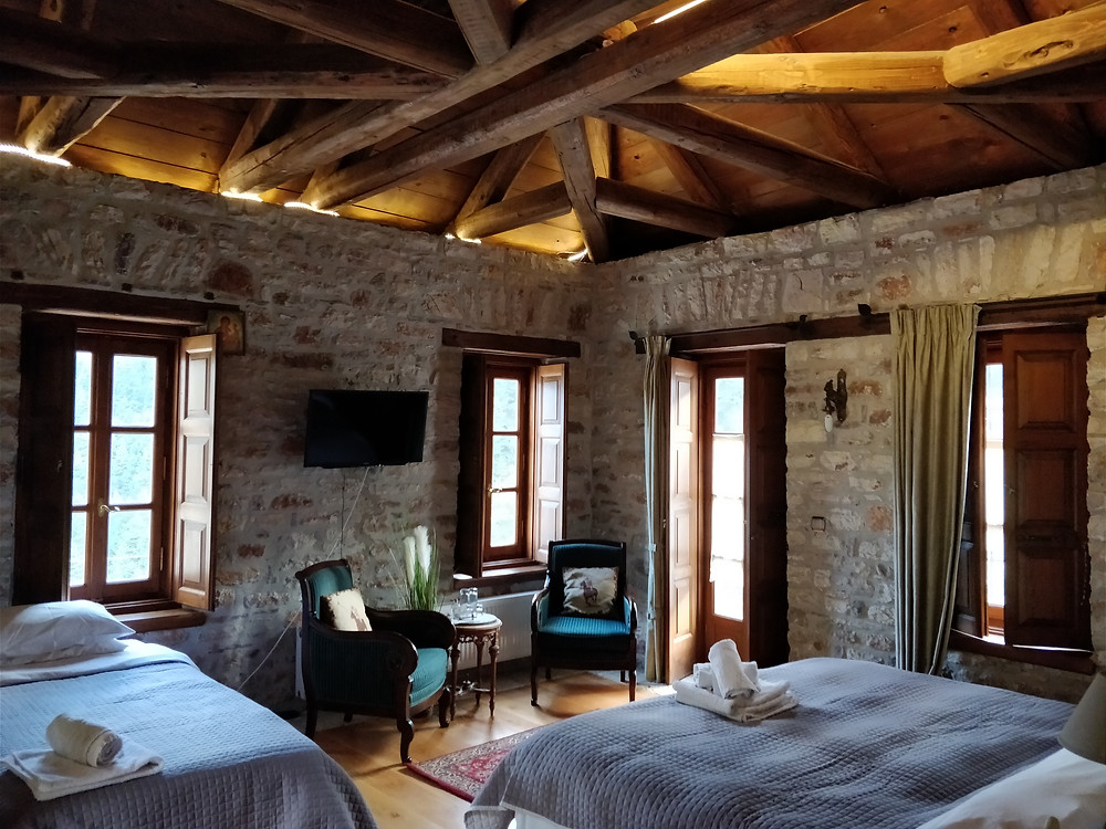 Two beds with white linens in rustic chic room in an eco-conscious hotel.