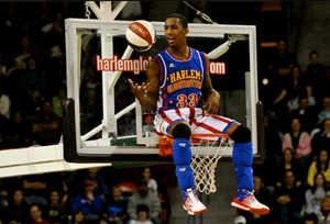 Harlem Globetrotter sitting on basketball hoop with a basketball during a performance