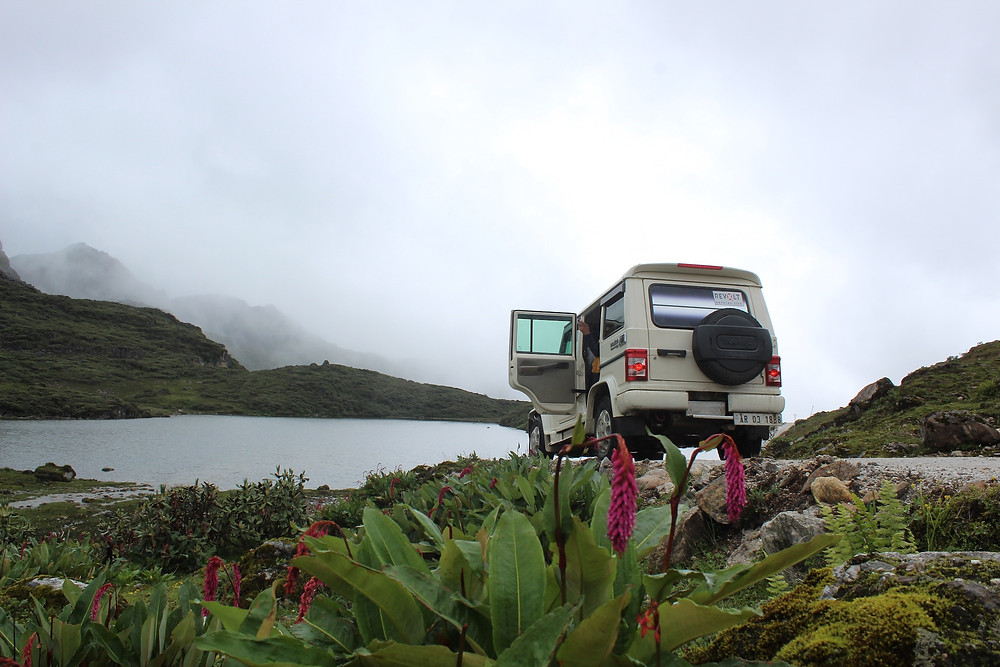 White Jeep in Central America by a foggy lake surrounded by lush vegetation.