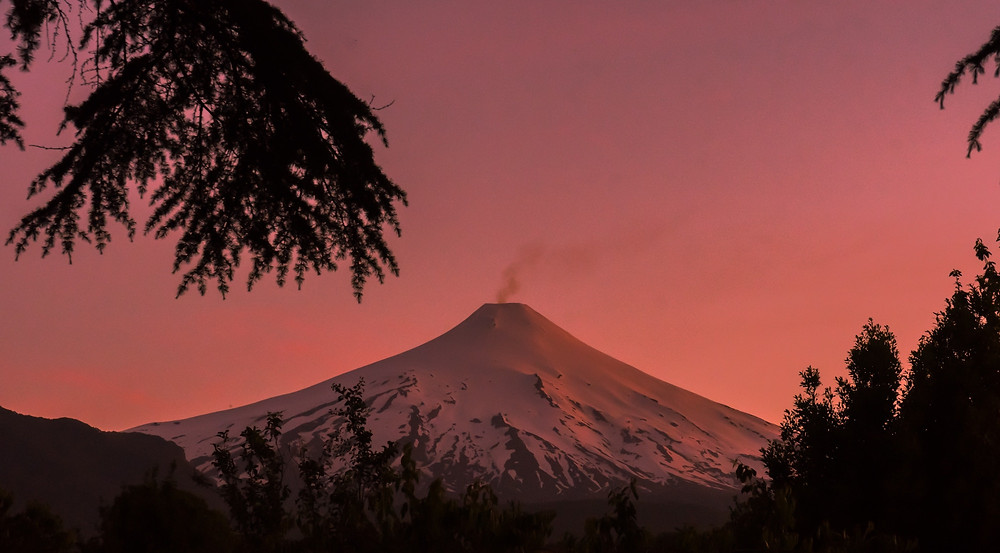Volcan Villarrica at sunrise with steam coming out of it.