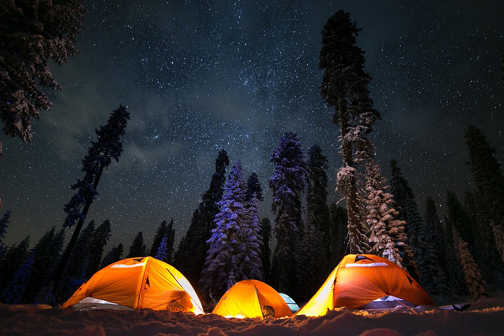 Starry night sky above three lit orange tents in the snow.