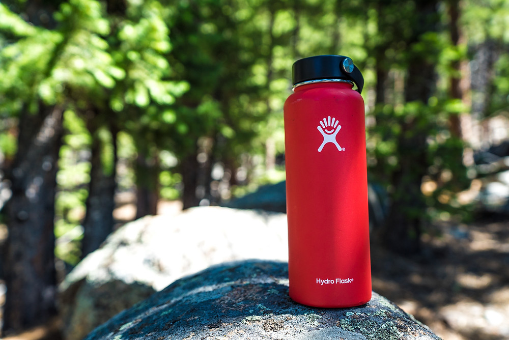 Red Hydroflask water bottle sitting on a rock during a camping trip.