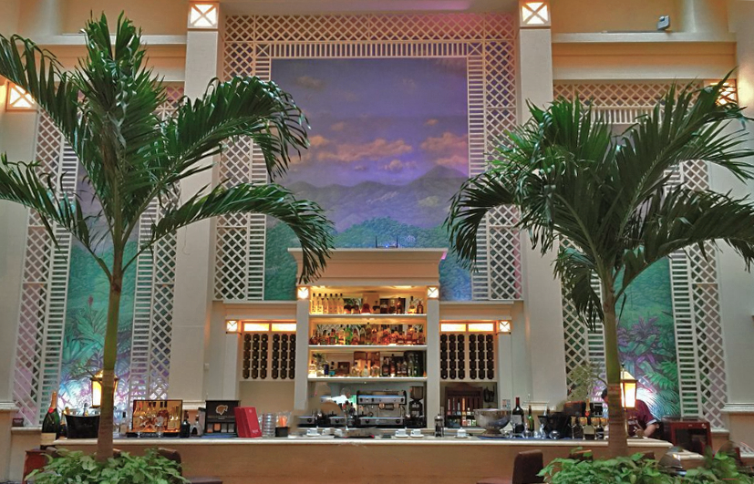 Backdrop and palm trees in Bar Mezzanine in Cuba's Hotel Saratoga.