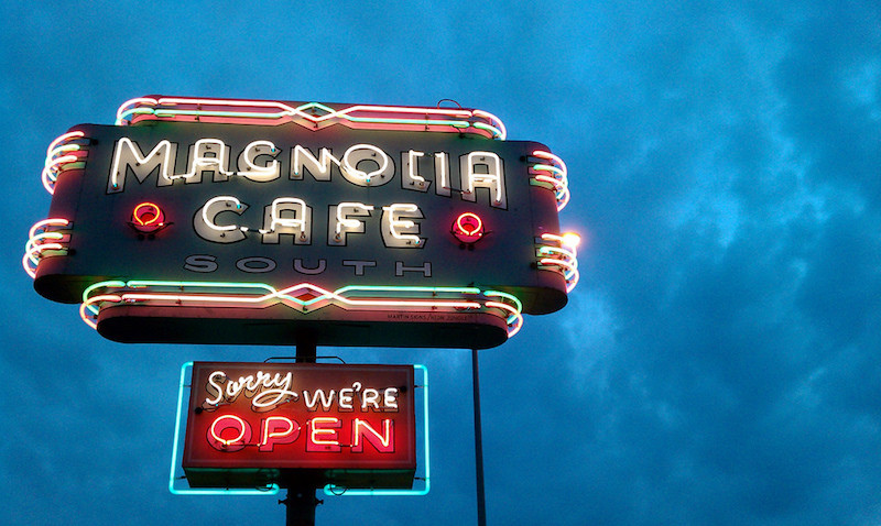 "Lit up sign for the Magnolia Cafe in Austin that says ""Sorry, We're Open."""