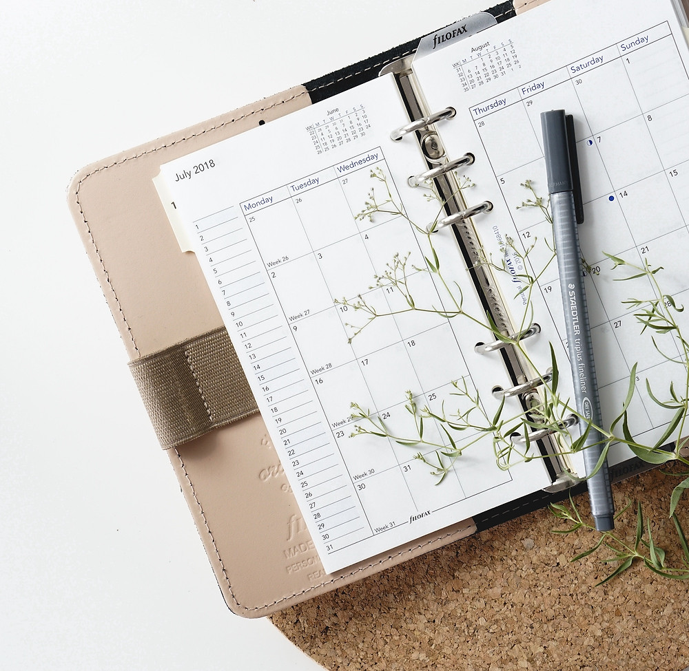 Beige day planner being used for travel planning that has a silver pen on it and a sprig of baby's breath.