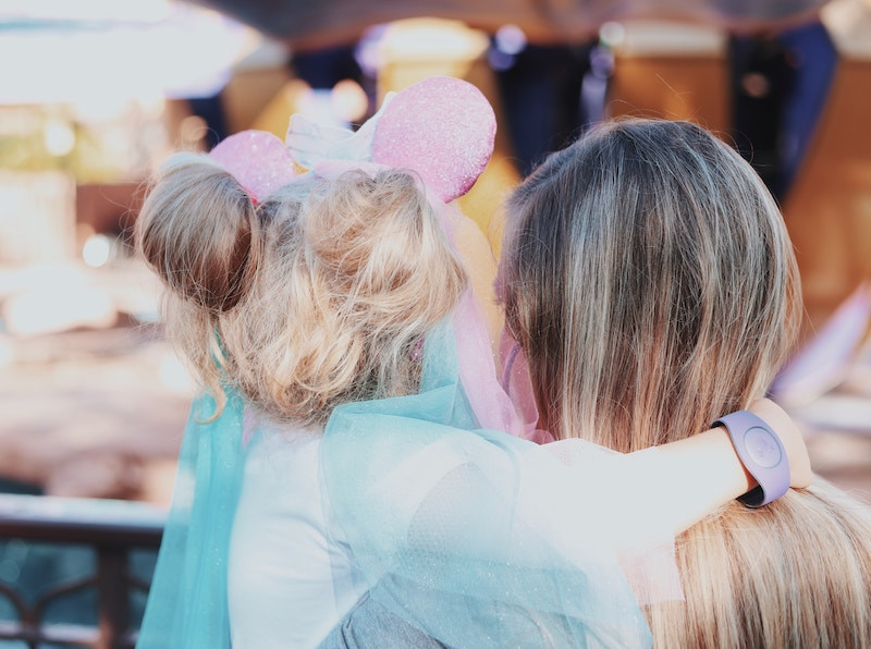 Blonde mother holding her blonde daughter in a blue princess dress and pink Minnie Mouse ears at Disney World