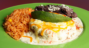 Fried, stuffed avocado on a green plate with rice and refried beans at Trudy's Tex-Mex in Austin.