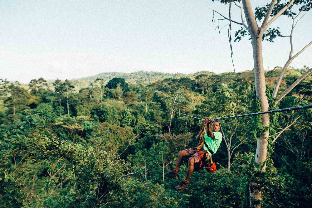 A man in a green shirt ziplining above the jungle.