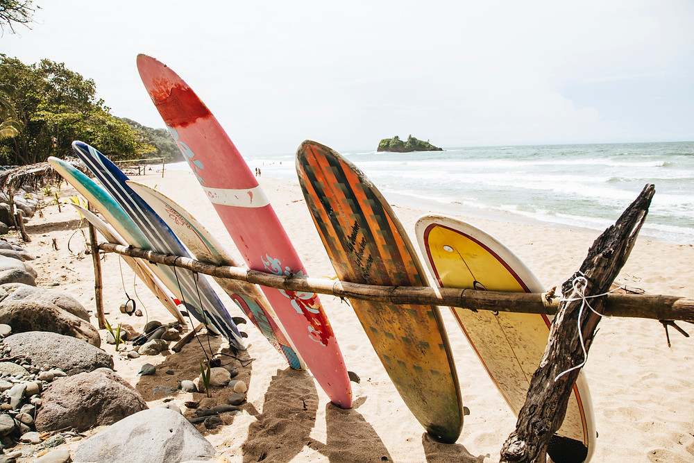 A variety of surfboards leaning against a post on the beach during a surf trip
