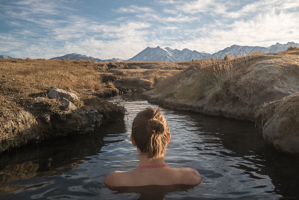 Woman soaking in natural hot springs near Mammoth Lakes, California