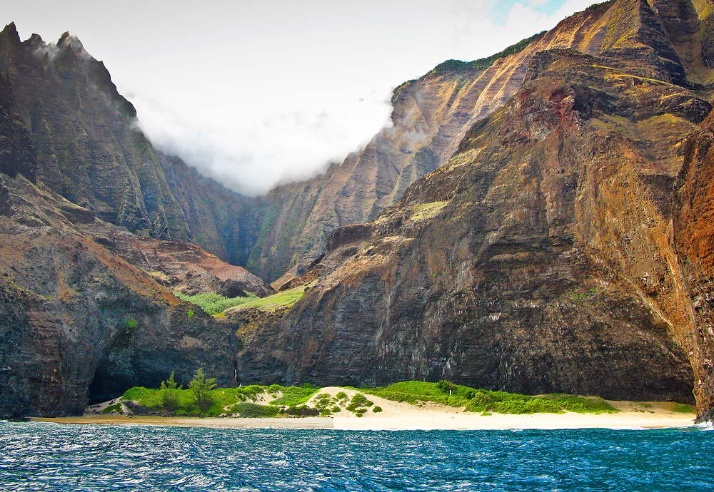 View from the ocean of the massive rock faces of the mountains backing Honopu Beach, Kauai.