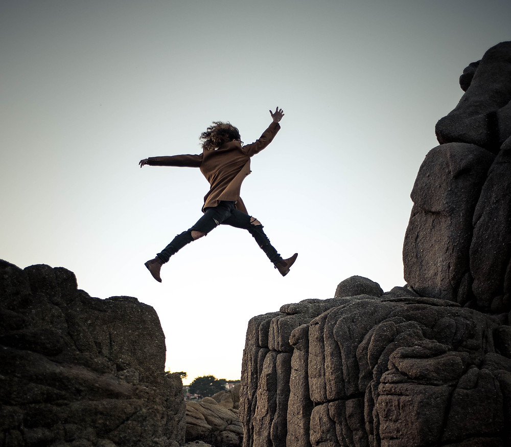 Woman in beige coat jumping across a rock because she's been empowered by traveling