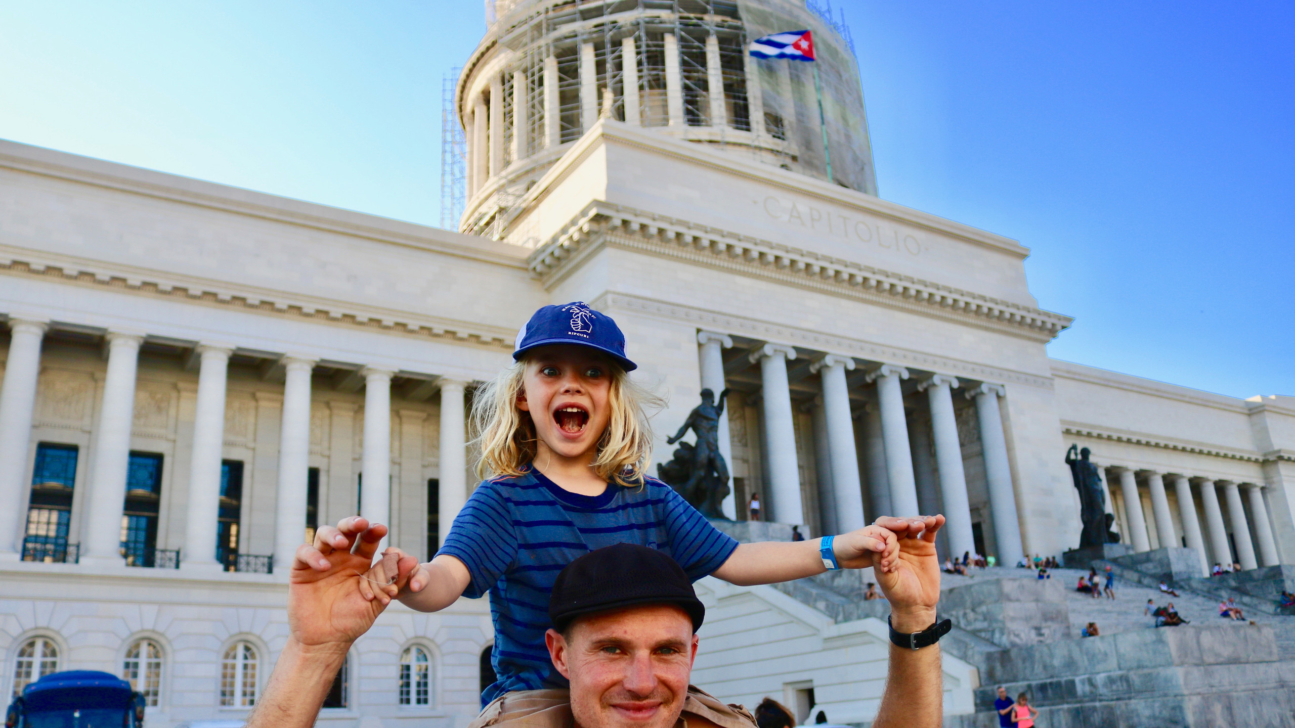 Little boy in blue striped shirt and blue baseball cap sitting on his dad's shoulders in front of El Capitolo in Havana.
