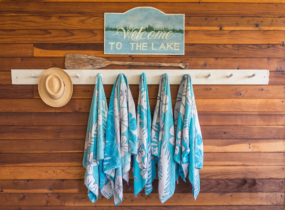 Five blue and white Hawaiian hibiscus print towels hanging on white pegs beneath a sign that says Welcome to the Lake.