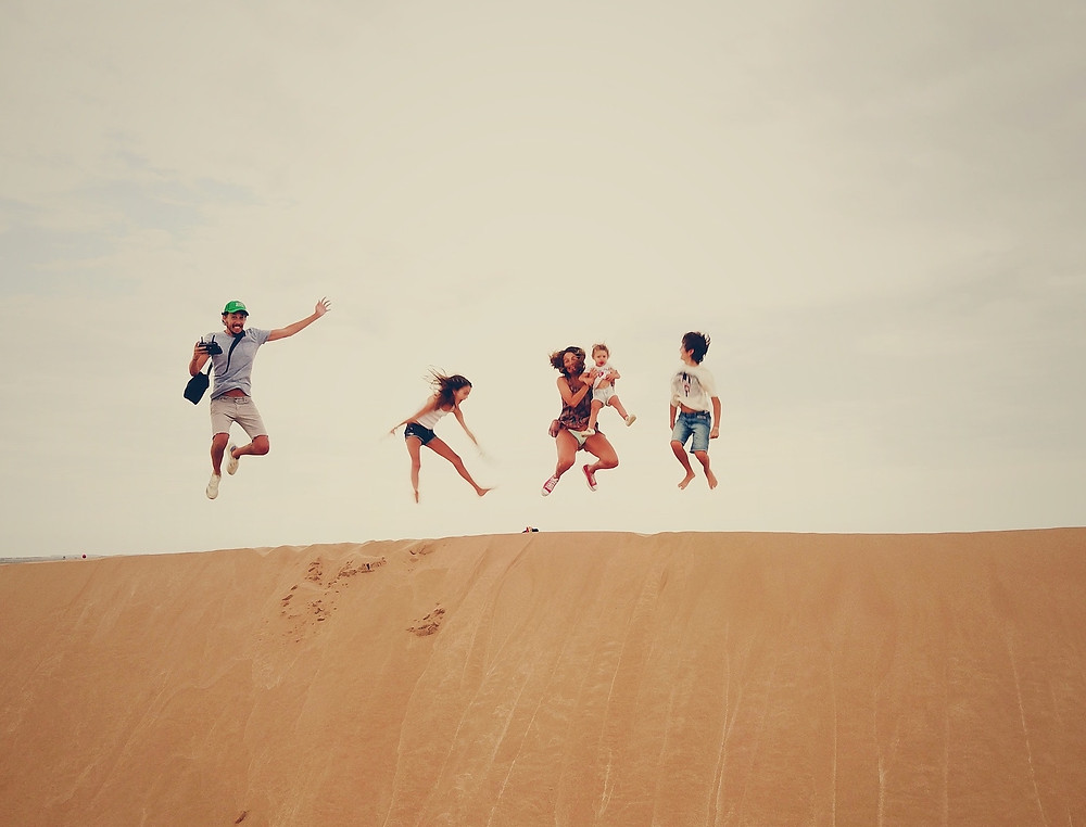 Family jumping on sand dunes while exploring a new location