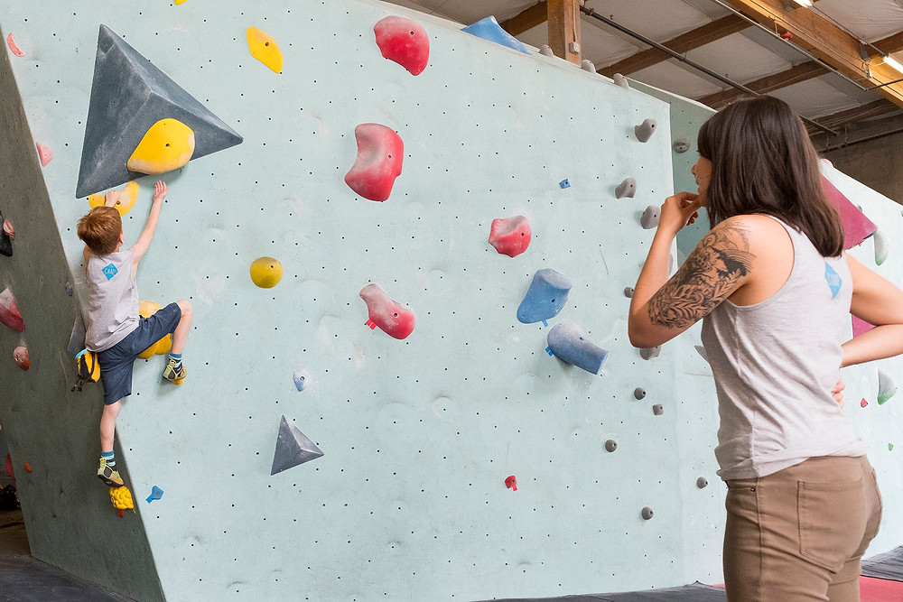 A mom watching a little boy climb at the Seattle Bouldering Project.