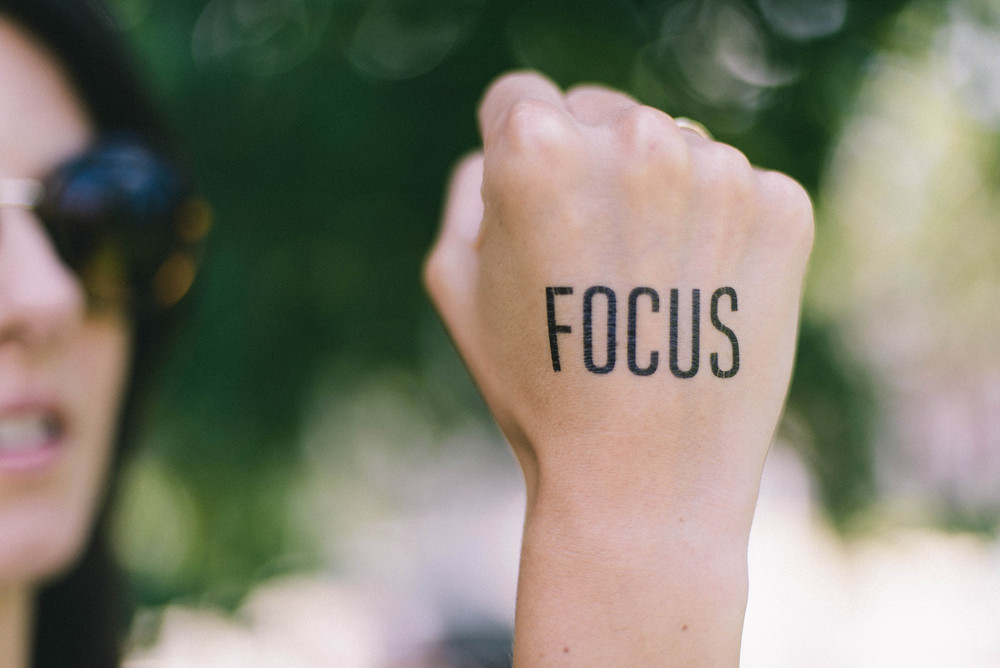 Woman with a tattoo that says Focus on her hand, inspiring focus during travel conversations