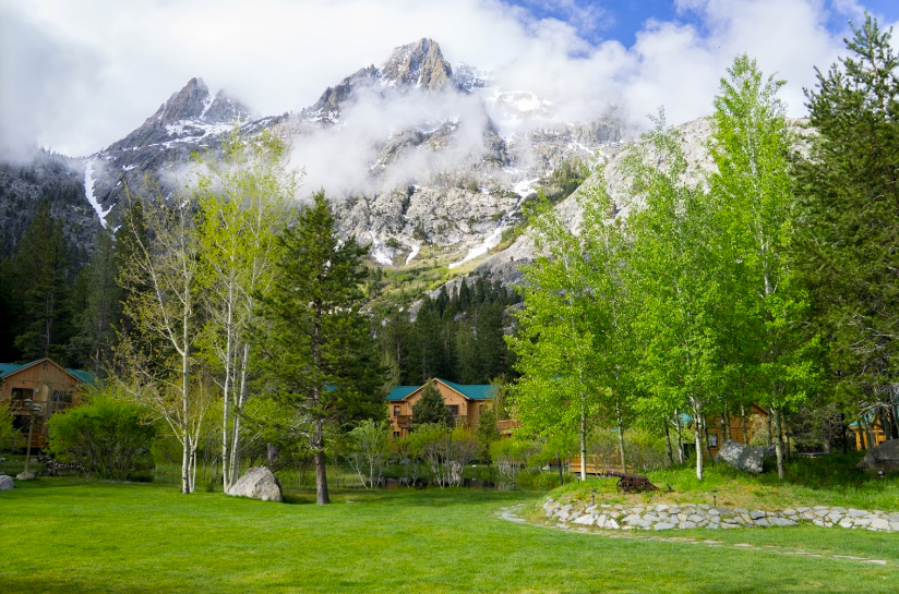 The Double Eagle Resort and Spa during spring when the lawn is covered in grass, and the Sierra Nevadas still have a bit of snow.