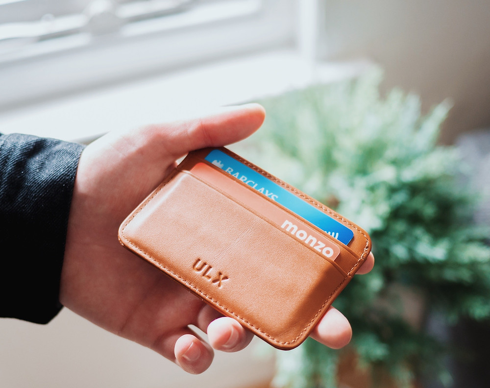 Man holding a brown leather bill fold with a blue credit card in it that is being used to purchase a cheap flight.