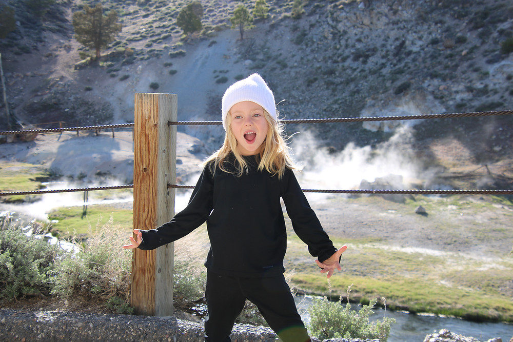 Blonde boy in black clothes and white beanie smiling on hiking trail at Hot Springs, near Mammoth Mountain.