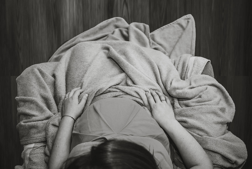 Pregnant woman with a blanket in her lap looking at her belly.