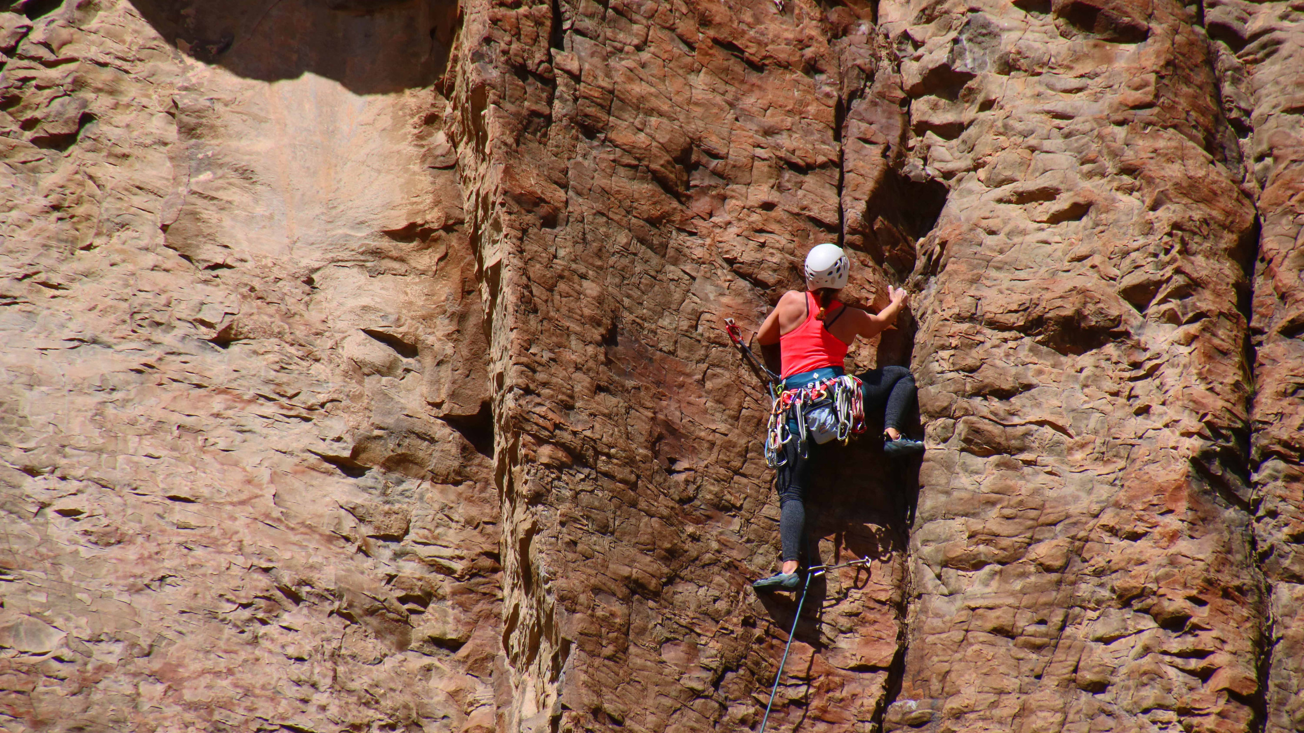Woman in red shirt and white helmet rock climbing in Diablo Canyon in Santa Fe, New Mexico