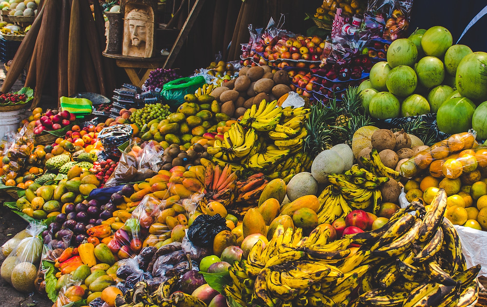 Eco-friendly farmer's market with bananas, papayas, mangoes, peaches and other fruits piled on top of each other