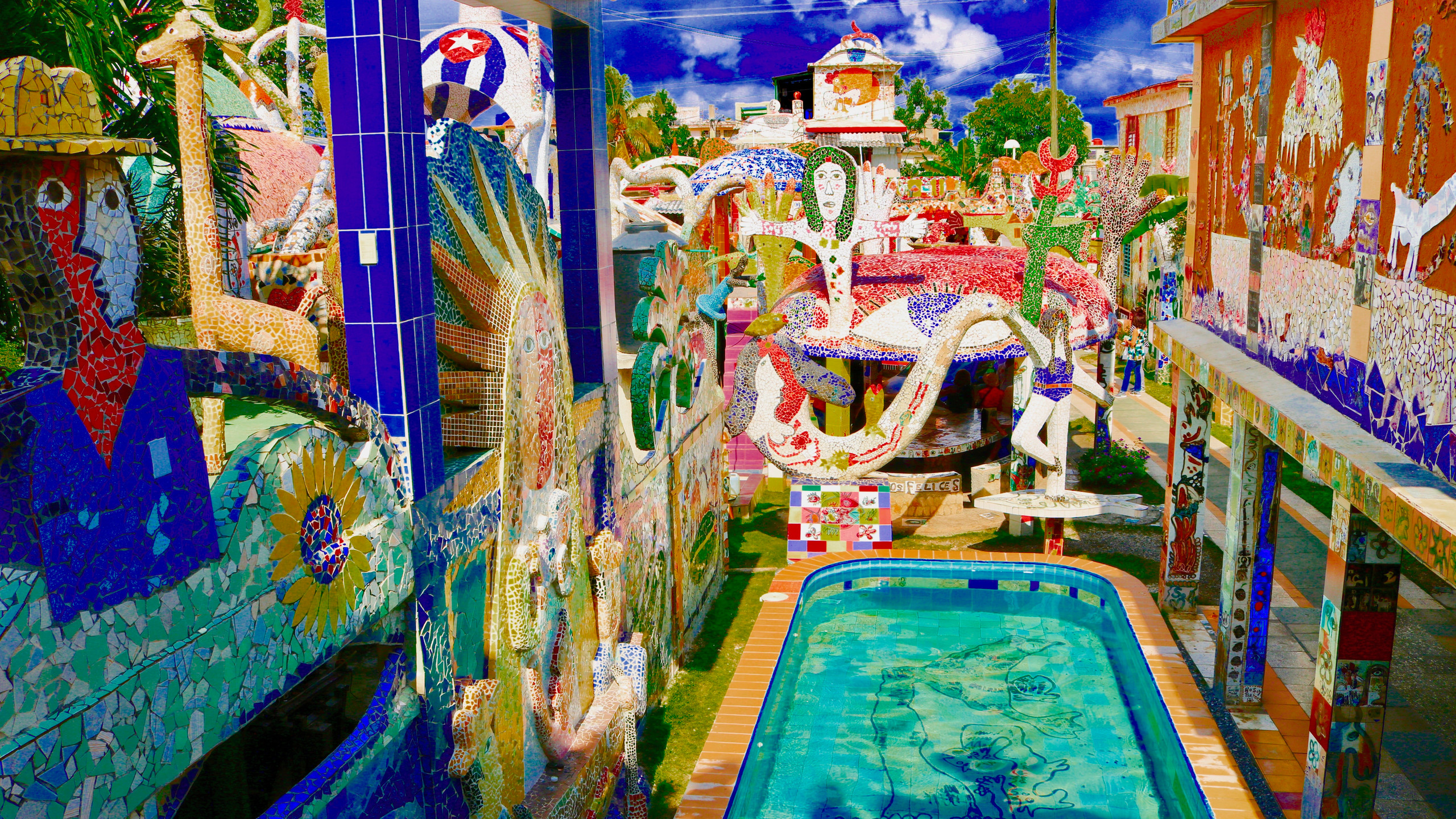 Pool surrounded by an entire structure covered in rainbow-hued mosaic tiles at Fusterlandia.