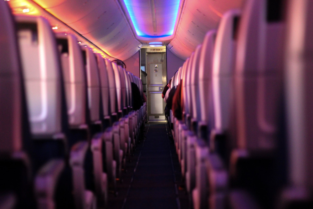 Empty seats on an airplane under a blue light.