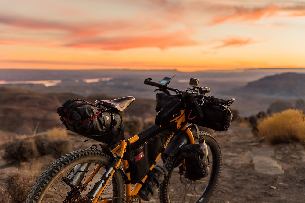 A mountain bike being used on an eco-conscious trip, on a hilltop at sunset