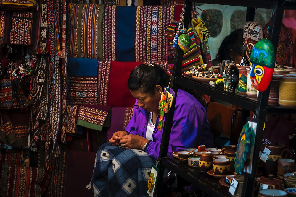 Woman weaving textiles in market in Cusco.