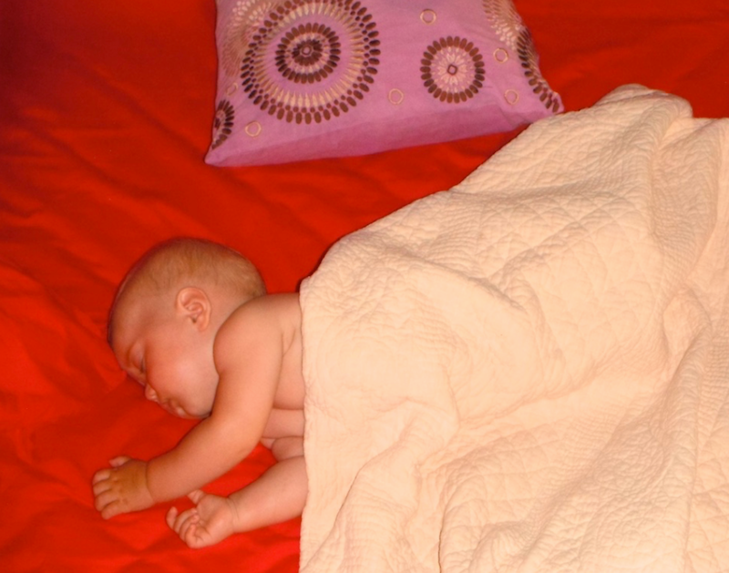 Blonde baby sleeping on red comforter in Costa Rica