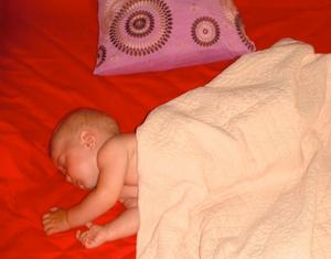 Blonde baby sleeping on red comforter in Costa Rica
