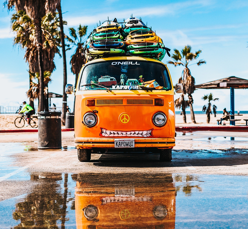 Van with surfboards at the beach being used for a surfing family vacation