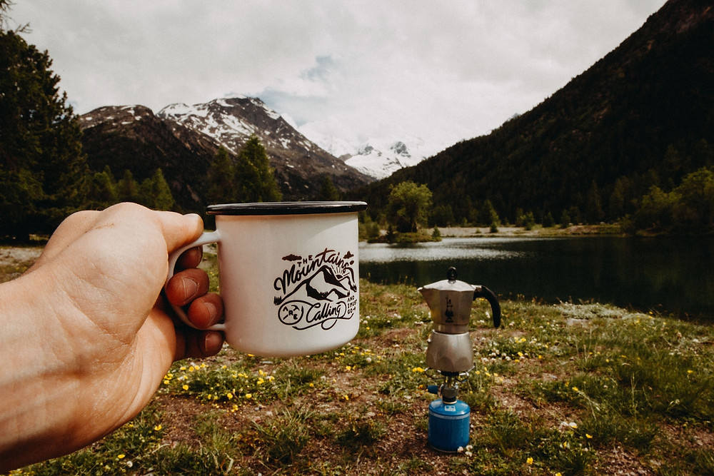 Man holding a white, metal coffee cup that says The Mountains Are Calling while camping.