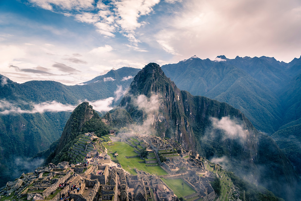 Machu Pichu with wispy clouds hugging it.