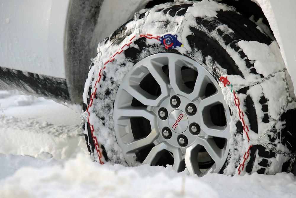 Red snow chains on a black GMC tire in the snow in Mammoth Mountain.
