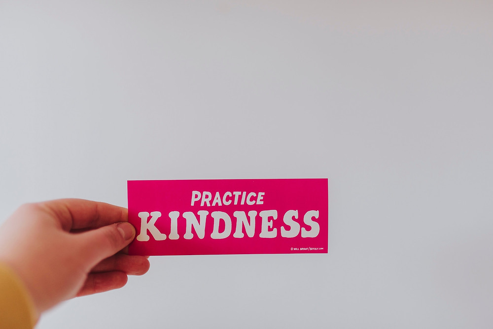 Pink sign that says practice kindness, reminding families to be kind while traveling